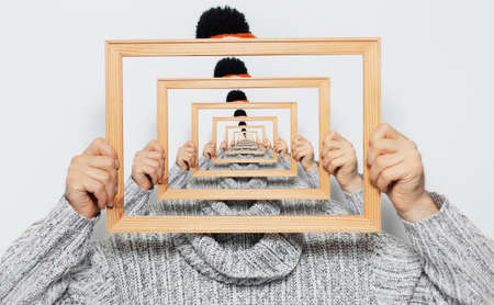 Enigmatic surrealistic optical illusion; portrait of young man holding frame on grey background.
