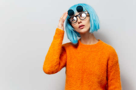 Studio portrait of young confident pretty girl with blue hair in orange sweater wearing sunglasses on white background.