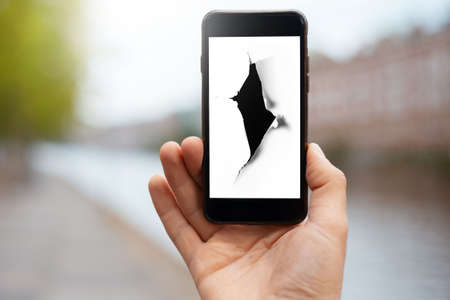 Close-up of male hand holding smartphone with hole in white paper on screen on blurred background of city.
