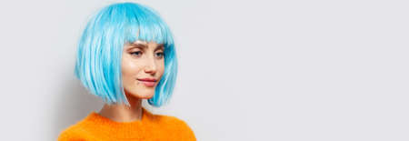 Studio portrait of young pretty girl with blue hair bob wearing orange sweater on white background. Panoramic banner view with copy space.