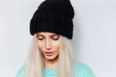 Close-up studio portrait of young pretty girl with blonde hair wearing black hat and blue sweater on white background. Stok Fotoğraf