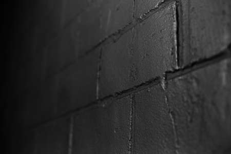 Close-up abstract background of textured black brick wall. Dark photo.