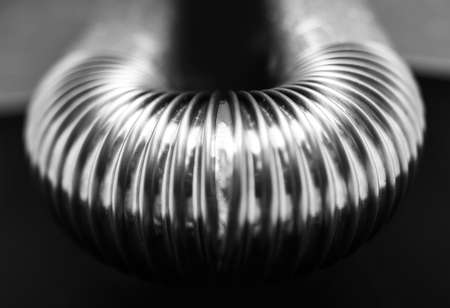 Black and white photo; close-up of stainless pipe on black-grey background.
