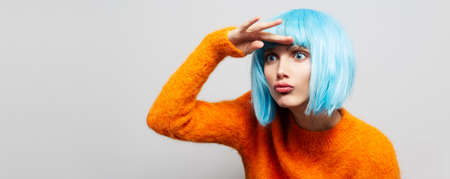 Studio portrait of young pretty girl looking away with hand on forehead, on white background. Wearing blue wig and orange sweater. Panoramic banner view.
