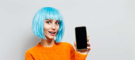 Portrait of young happy girl holding smartphone in hand, wearing blue hair wig and orange sweater on white background with copy space. Panoramic banner view. Stok Fotoğraf