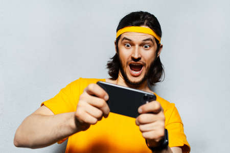 Studio portrait of young surprised man with long hair, playing game on smartphone on grey textured background; wearing yellow band for head and shirt.