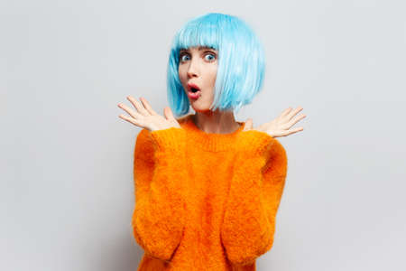Studio portrait of young surprised girl with blue hair in orange sweater on white background.