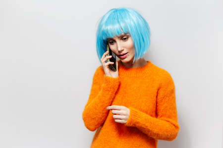 Studio portrait of young pretty girl talking on smartphone, wearing blue hair wig and orange sweater on white background.