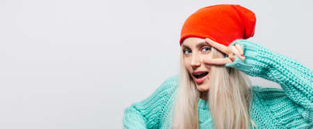 Studio portrait of happy young blonde girl showing peace sign on white background. Wearing orange hat and blue sweater.