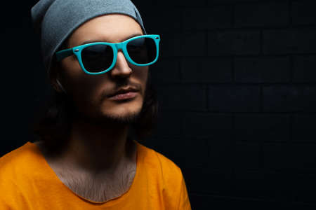 Close-up portrait of serious young man on black background; wearing blue sunglasses, grey hat and orange shirt.