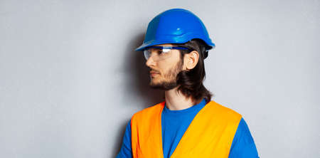 Studio side portrait of young confident man, construction worker engineer wearing safety equipment on textured background of grey. Panoramic banner view.