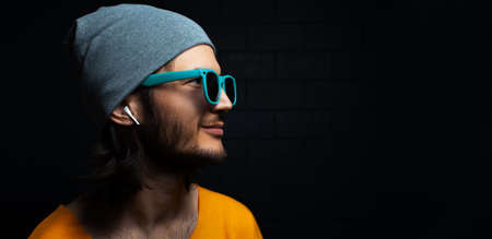 Close-up portrait of young smiling man with wireless earphone in ear on black background; wearing blue sunglasses. Panoramic banner view with copy space.