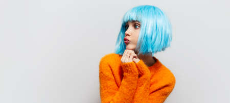 Portrait of young pretty girl with blue hair in orange sweater on white background with copy space. Panoramic banner view.
