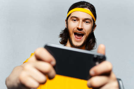 Close-up studio portrait of young excited man playing game on smartphone on grey textured background.