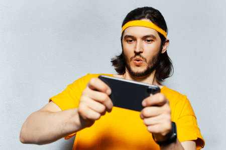 Studio portrait of young excited man playing game on smartphone on grey textured background; wearing yellow band for head and shirt.