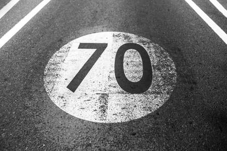 Black and white photo of old shabby speed limit sign with 70 km per hour, painted on asphalting road.
