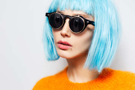 Close-up studio portrait of pretty girl with blue hair, wearing round black sunglasses and orange shirt on white background. Fashion concept.