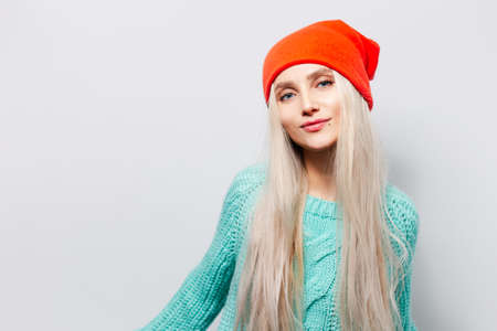 Studio portrait of young blonde girl wearing orange hat and blue sweater on white background.