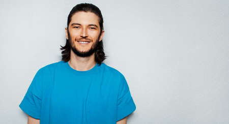 Portrait of young smiling man with long hair in blue shirt on textured background of grey  with copy space.