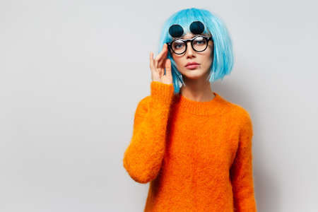 Studio portrait of young beautiful pretty girl with blue hair in orange sweater wearing sunglasses on white background. Holding hand on glasses.