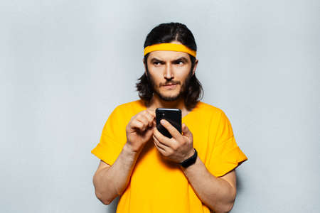 Portrait of young man touching on screen of smartphone, looking thoughtful away, wearing yellow shirt and head band on textured background of grey.