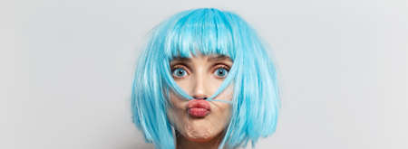 Studio portrait of young pretty girl with blue hair, sending blowing kiss on white background. Panoramic banner view.