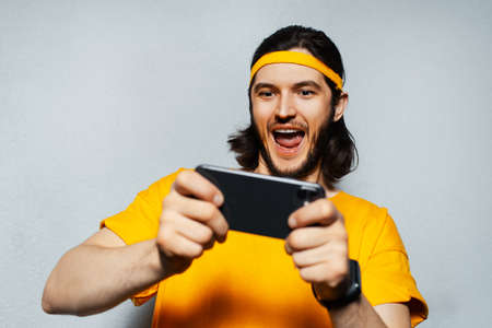 Studio portrait of young happiness man in yellow, playing game on smartphone on grey background.