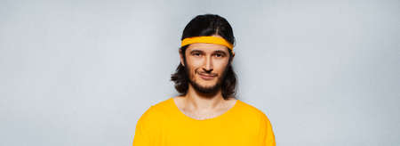 Panoramic banner portrait of young confident man in yellow with long hair on grey textured background.