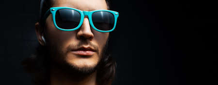 Close-up portrait of young serious man with wireless earphone in ear on black background; wearing blue sunglasses.