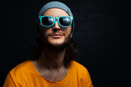 Portrait of young smiling man on black background, wearing blue sunglasses and orange shirt.