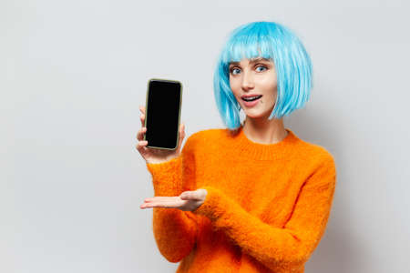 Studio portrait of young happy girl showing on smartphone, wearing blue hair wig and orange sweater on white background. Stok Fotoğraf