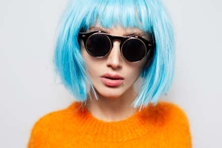 Close-up studio portrait of fashionable pretty girl with blue hair, wearing round sunglasses and orange shirt on white background.