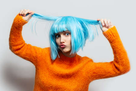Studio portrait of young funny girl with blue hair, in orange sweater on white background.