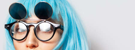 Half face concept; close-up portrait of beautiful eyes of young girl with blue hair wearing round sunglasses on white background. Stok Fotoğraf