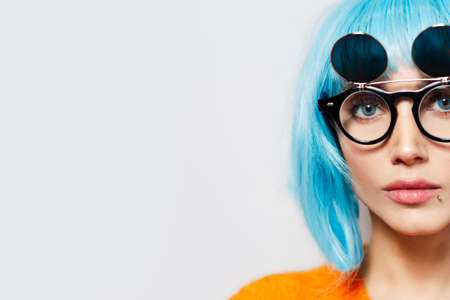 Half face concept; close-up studio portrait of young pretty young girl with blue hair, wearing round sunglasses and orange shirt on white background with copy space. Stok Fotoğraf
