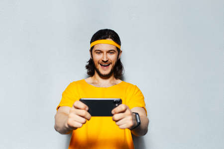 Studio portrait of young happy man in yellow with long hair, playing game on smartphone on grey background. Stok Fotoğraf