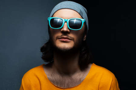 Portrait of young man on black and grey background, wearing blue sunglasses, hat and orange shirt.