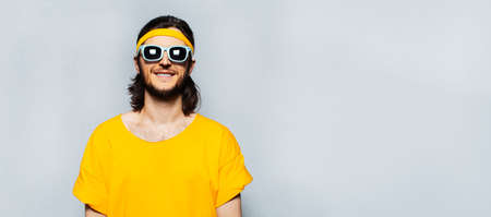 Panoramic banner portrait of young happy man in yellow with sunglasses on textured background of grey with copy space. Stok Fotoğraf