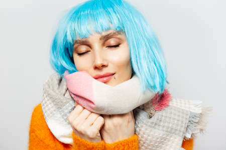 Close-up studio portrait of young pretty girl with closed eyes wearing scarf and blue wig, feeling warm, on background of white. Stok Fotoğraf