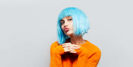 Studio portrait of young beautiful girl with blue hair in orange sweater on white background. Sending blowing kisses.