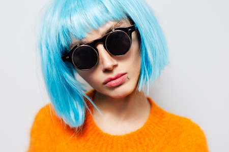 Close-up studio portrait of cool pretty girl with blue hair, wearing round sunglasses and orange shirt on white background.