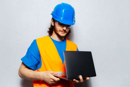 Portrait of young man construction worker engineer wearing safety equipment, holding laptop on textured background of grey.