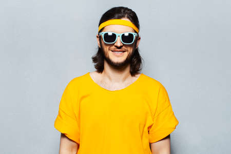 Portrait of young smiling man in yellow wearing sunglasses on textured background of grey. Stok Fotoğraf