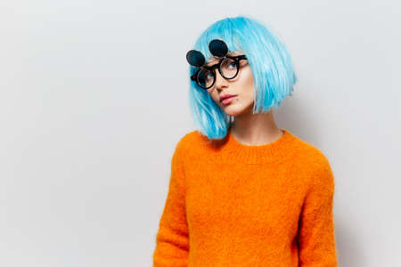 Portrait of young beauty girl with blue hair in orange sweater wearing sunglasses on white background.