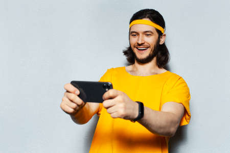 Studio portrait of young excited man playing game on smartphone, on grey textured background; wearing smartwatch, yellow band for head and shirt.