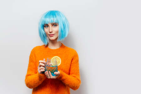 Portrait of young pretty girl with blue wig, holding glass mug with juice and piece of lemon.