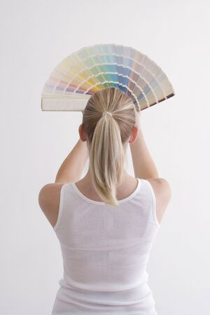 Woman with a fanned swatch book staring at a white wall. photo