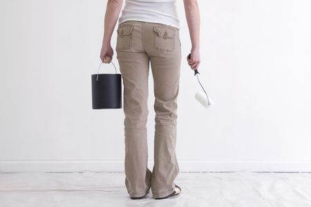 chinos: Hortizontal image of woman from waist down with her back facing the camera.  She is holding a paint can and roller, facing a white wall. Stock Photo