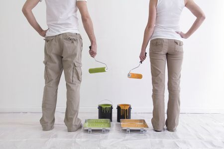 chinos: Man and Woman facing a white wall with paint cans and rollers ready to paint.  Their backs are facing the cameral and they are only shown from the waist down.