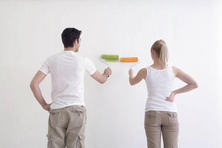 chinos: Man and Woman facing a white wall with their paint rollers getting ready to paint.  Their backs are facing the camera.